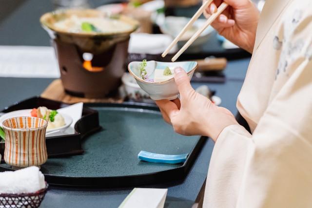 和食を食べる着物姿の女性
