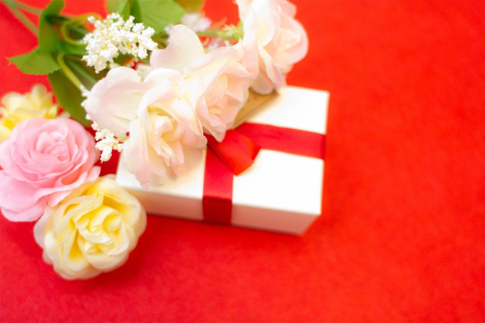 赤い台紙の上に置かれたプレゼントと花