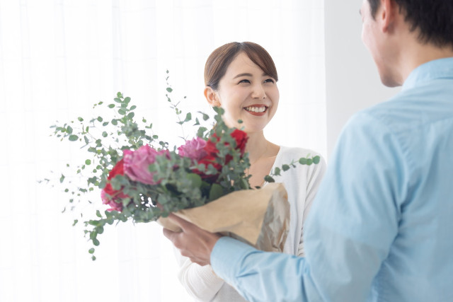 笑顔で花束を持つ女性と男性